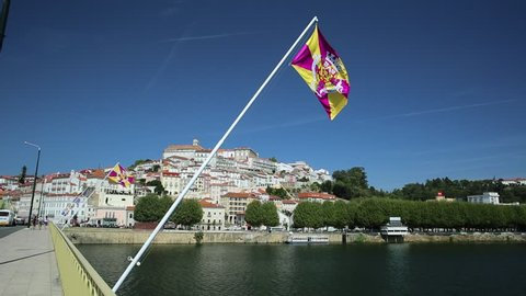 POV walking in old Coimbra city and Mondego river from Santa Clara bridge with flags of Coimbra flying on foreground. Coimbra is famous for its University, founded in 1290, among the first in Europe