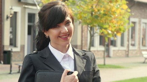 Beautiful smiling business woman on the background of the modern office. Holding tablet. Appartment rental agent concept.