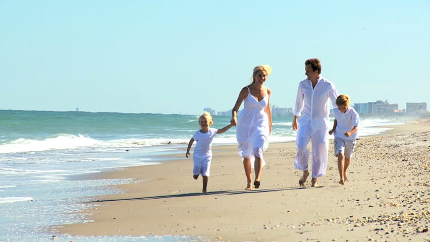 Young blonde family having fun playing on the beach