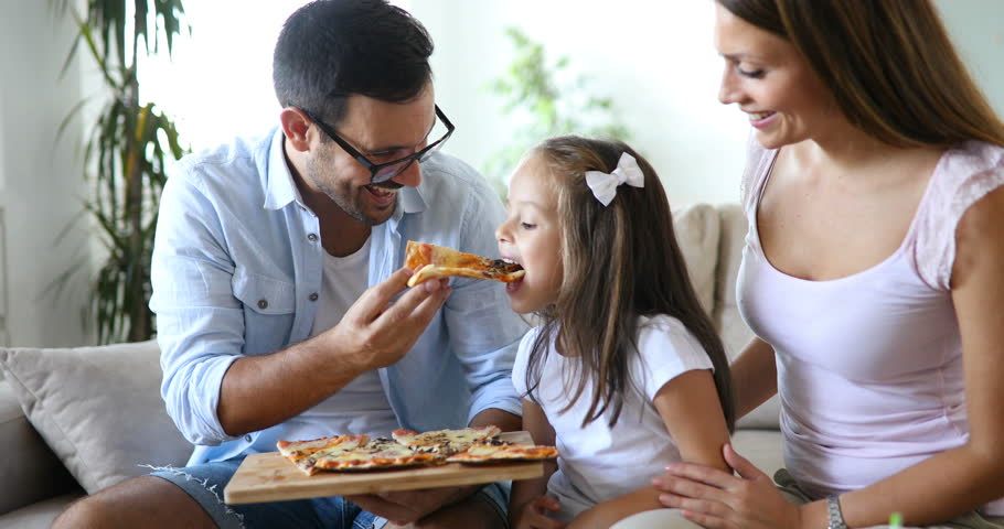 family eating pizza - 910×480