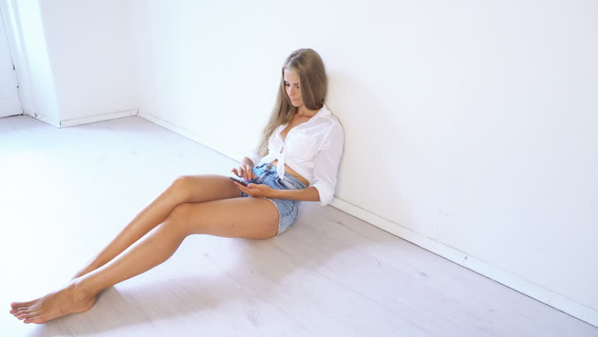 Beautiful girl sitting on the floor and talking on the phone Internet | Shutterstock HD Video #32079283