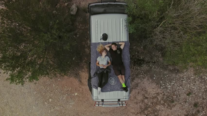 Top view with zoom out on romantic couple on date, laying on roof of car or van, watch stars or sky in natural national park, secluded camping site in wilderness, concept relationship goals or | Shutterstock HD Video #32080243