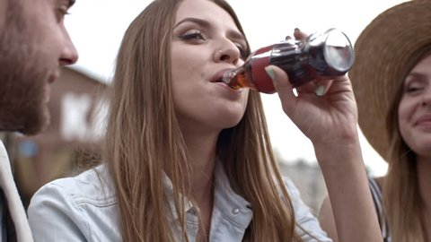 Tilt up of pretty young woman drinking coke from glass bottle and eating pizza while chatting with friends outdoors