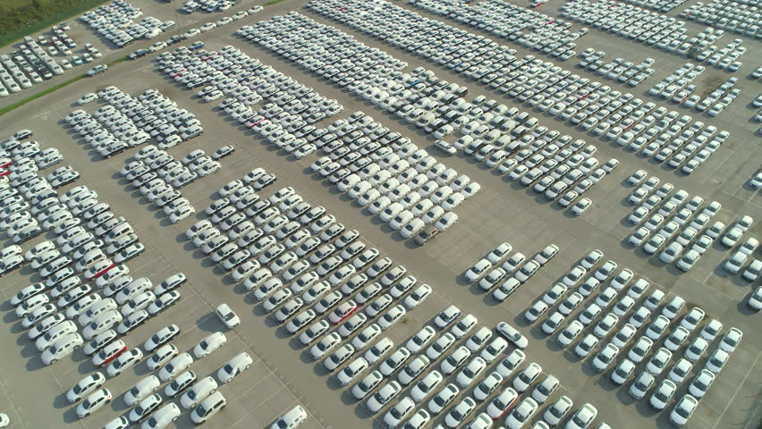 AERIAL: Flying over big industrial zone with big parking lot of brand new cars. Many white cars waiting for sale and transportation at big sea port parking space. Automobile industry. | Shutterstock HD Video #32093131