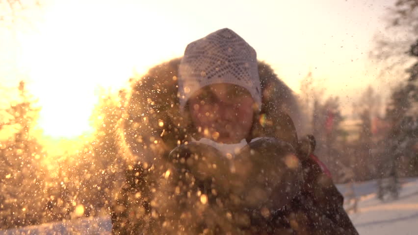 SLOW MOTION CLOSE UP: Young woman blowing snowflakes over the setting sun in winter. Smiling girl sending a snow kiss on gorgeous sunny day on winter evening. Playful girl blowing snowflakes at sunset
