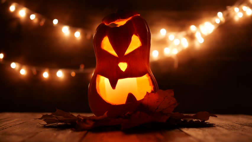 Carved Halloween pumpkin with lights on background. Dark key footage in UltraHd resolution.