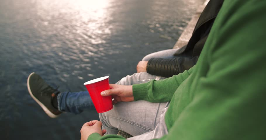 Happy friends hanging out and drinking outside. Two young men or boys sitting and drinking from red party cups. Guys night out at beach, lake or sea.