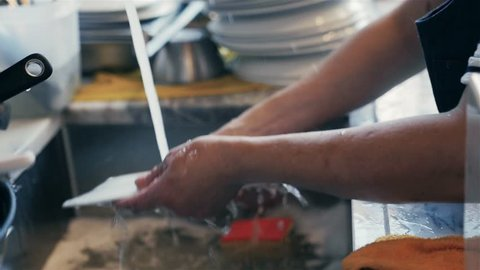 Woman washing dishes in the kitchen. Close up of woman hand. Housewife clean dishes. Modern restaurant.