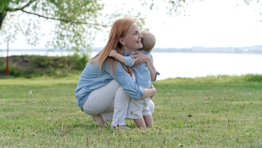 Tracking of adorable toddler boy with blond hair walking barefoot on green grass towards happy young mother, then hugging with her