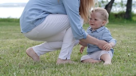 Tracking of adorable toddler boy with blond hair walking barefoot on green grass towards young mother, then falling down and crying