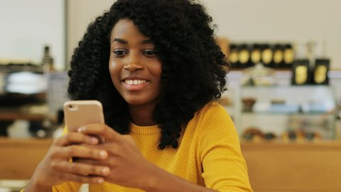 Close up portrait of the beautiful afro-american girl holding her mobile, surfing the Internet and texting her friends in the vintage cafe. Indoor.