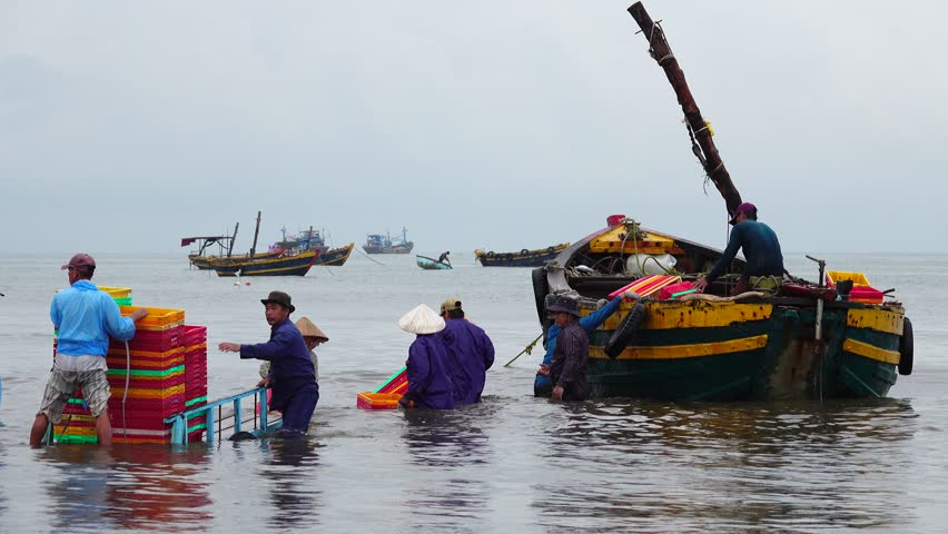 Long Hai market, Ba Ria, Viet Nam - August 15, 2017: Local people working at marketplace, woman is selective fish and man is carrying basket fresh fish from ship on the beach