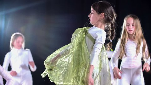 Girls are wearing white costumes and they are performing a hip hop routine on stage. They're dancing in front of a large audience.