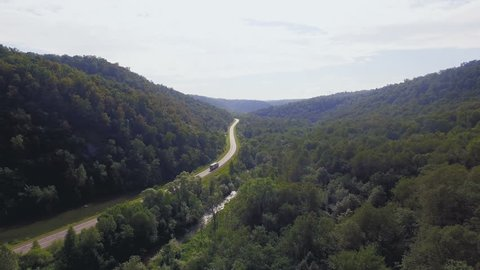 AERIAL: Trucker moves among wild mountain forest. Camera fly above green trees to the curvy road behind semi-truck. Cargo transportation, nature landscape in sunny moment of summer.