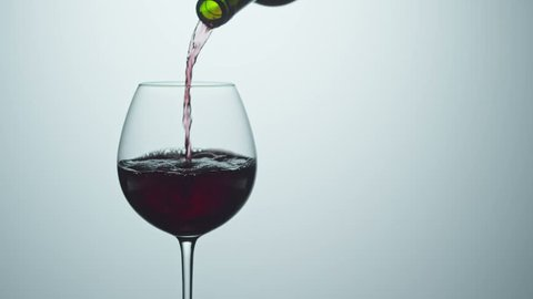 Cinemagraph of filling wineglass with red wine from the bottle. Closeup shot