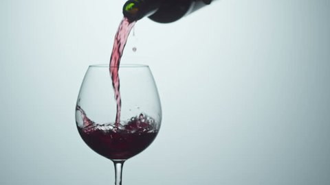 Cinemagraph of pouring red wine into wineglass from bottle. Studio shot