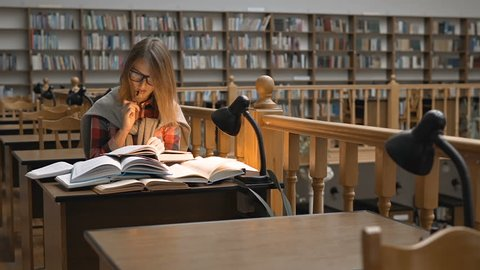 Pretty successful student wears glasses studying with books in the library