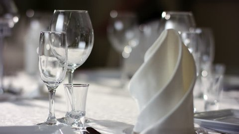 Shot of napkins and wine glasses banquet table at luxury restaurant