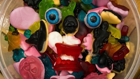 A halloween candy monster in a bowl of haloween candy eyeballs glaring at one on top of sweets.
