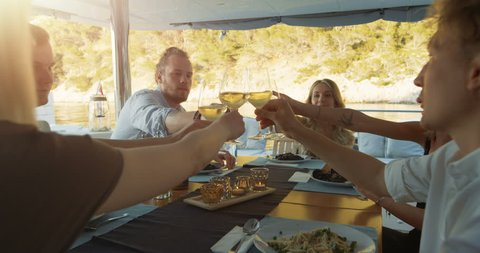 Company of Young People on a Yacht, They Clink Glasses in Celebration. Table Served with Steamed Mussels. Beautiful Seaside View. Shot on RED Epic 4K UHD Camera.