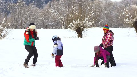 Two happy families have fun playing in the snow. Moms and their children.