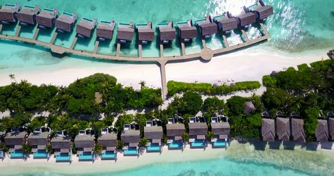 v09560 five 5 star resort water bungalows in Maldives with drone aerial flying view on white sand beach on tropical island