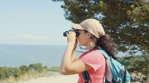 Travel woman looking at wildlife with binoculars. Woman on vacation looking at nature landscape. Hiker with a backpack is looking through binoculars at sea, at beautiful landscape. Mountain. Beach.