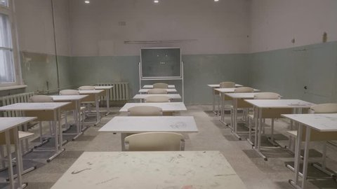 Empty classroom with wooden desks, white and green chalk boards in school. empty classroom. Abandoned School classroom with school desks and blackboard