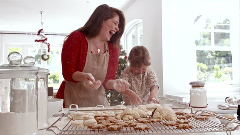 Smiling mother and daughter playing with cookie flour at kitchen counter while making Christmas cookies. Baked cookies and muffins on tray for Christmas.