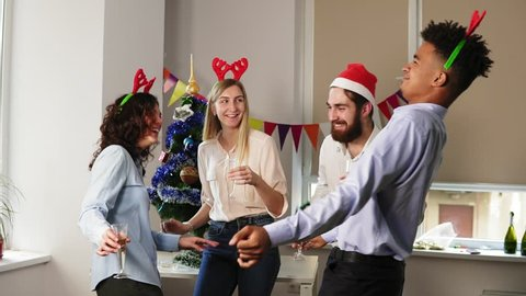 Having fun during corporate New Year party in the office: Multiracial group of happy office workers dancing during corporate New Year party wearing santa hats, holding glasses with sparkling wine