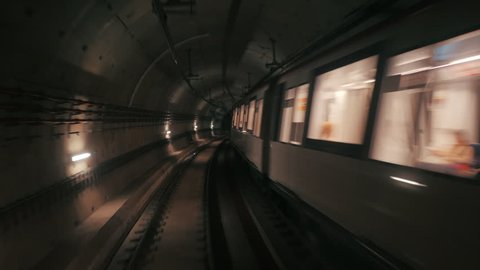 View of subway tunnel as seen from reverse of moving backward train. Fast underground train riding in tunnel of modern city. Long footage of underground train in Barcelona following its route