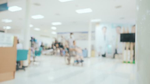 Locked shot and blurred with Scene inside the hospital, Someone has to push the wheelchair with patient and other people walk around the hall way