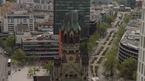 May, 2017 Berlin, Germany. The Kaiser Wilhelm Memorial Church during the day with street traffic and an aerial move.
