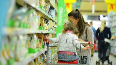 Indoors Portrait of Young Attractive Mom and Little Child Buying Food in a Supermarket. Side View of Happy Family Choosing Products with Shopping Cart.