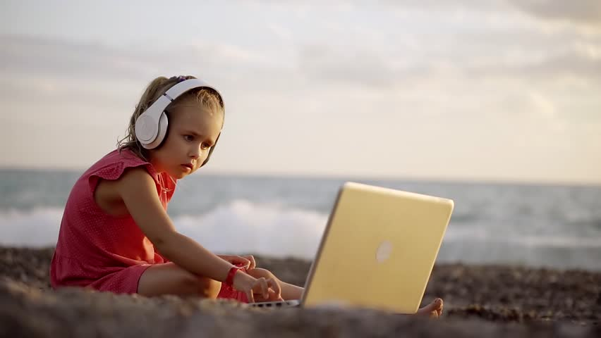 Little Girl Is Sitting On The Beach Near The Sea And Is Watching A Cartoon On