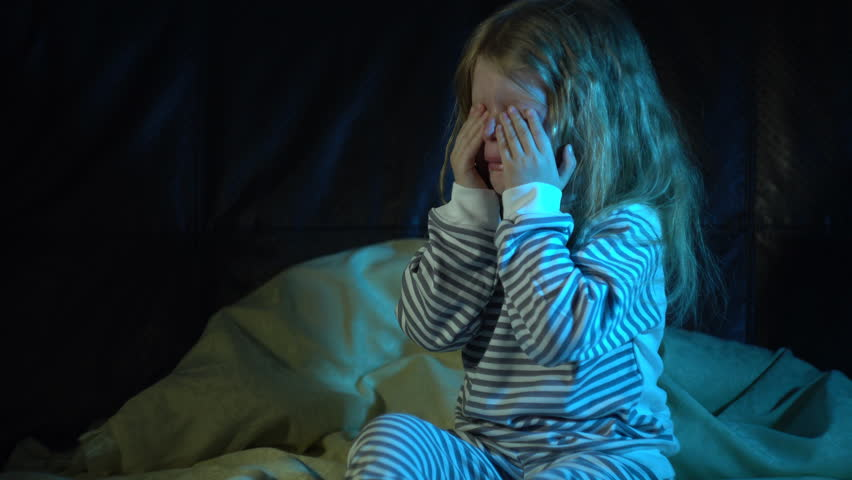 A upset little girl in striped pajamas sits on the bed at night in her room and cries covering her face with her hands, then wipes away her tears and tries to calm down.