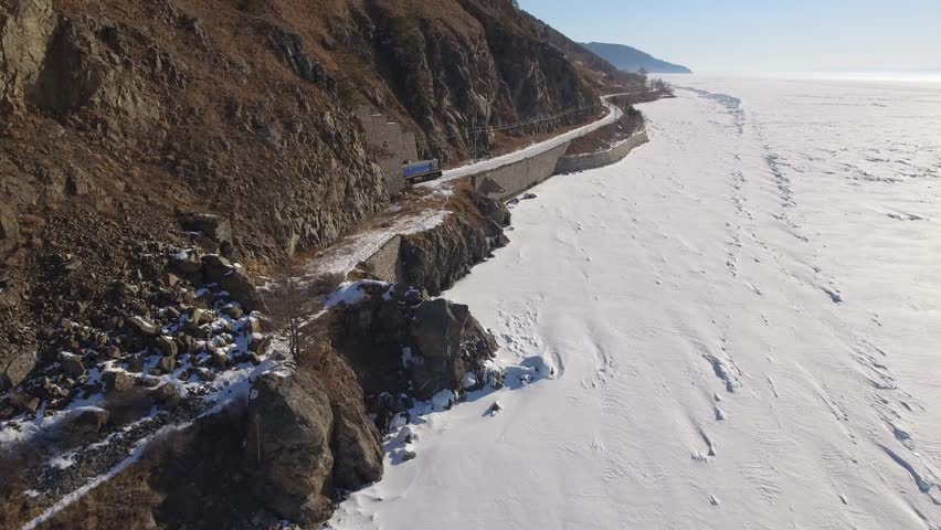 Train from tunnel tourist destination passenger. Baikal lake Russia Siberia. Largest ice freshwater lake Transbaikalia TRANS-Siberian railway  High mountains snow. Day winter Blue sky. Aerial Drone