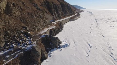 Train from tunnel tourist destination passenger. Baikal lake Russia Siberia. Largest ice freshwater lake Transbaikalia TRANS-Siberian railway  High mountains snow. Day winter Blue sky. Aerial Drone