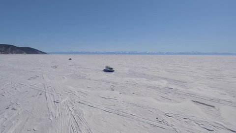 Khivus boat hovercraft tourist attraction. Baikal largest freshwater lake Field Russia Siberia Frozen. Landscape space High rocks. Close to approaching. Snow winter sunny. Best Aerial Drone