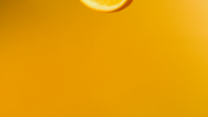 Sliced orange falling into orange juice shooting with high speed camera.