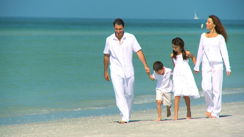 Attractive healthy young family enjoying time together walking outdoors on the beach filmed at 60FPS | Shutterstock HD Video #3230593
