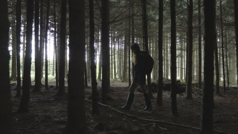 Young woman walk slowly through the trees in the forest