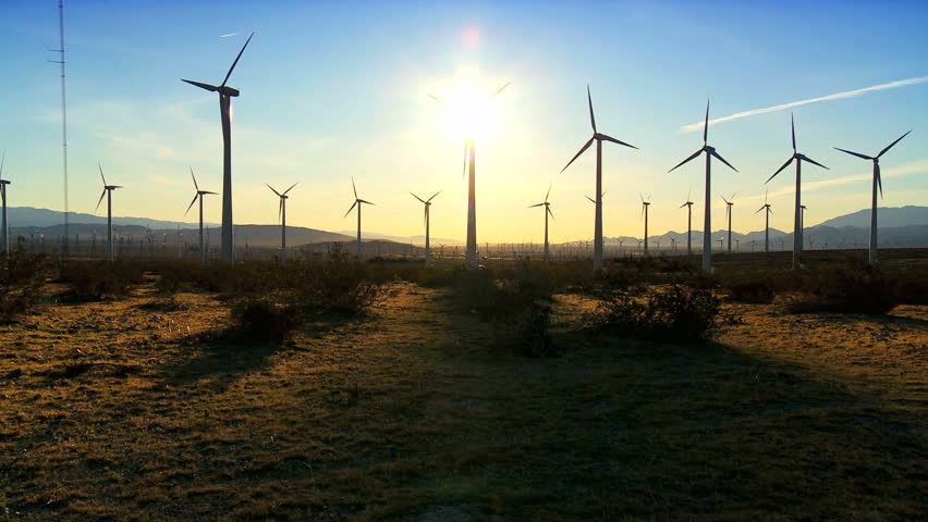 Wind turbines producing clean alternative energy in silhouette at dusk
