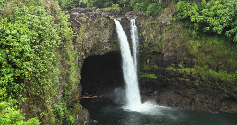 Beautiful Rainbow Falls Hilo Hawaii tropical stream. Big Island, largest, most volcanic active location. Rain forest environment and landscape. River stream with waterfalls. Beautiful green landscape.