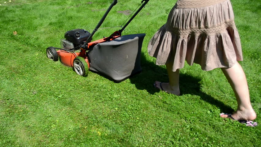walk woman girl in skirt and flip-flop shoes cut lawn grass mower in yard.