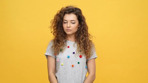 Young curly woman in t-shirt sating no and holding crossed arms over yellow background