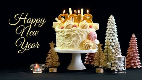 2018 Happy New Year showstopper cake decorated with white chocolate frosting, cookies and candy centerpiece on a festive table, with animated text.