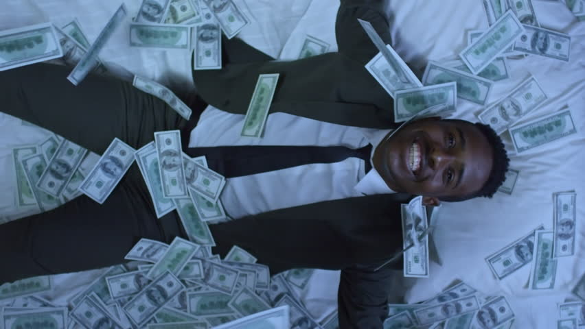 Directly above shot of African-American businessman in suit sleeping in bed, then waking up and smiling with happiness as money raining on him from above | Shutterstock HD Video #32393143