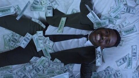 Directly above shot of African-American businessman in suit sleeping in bed, then waking up and smiling with happiness as money raining on him from above