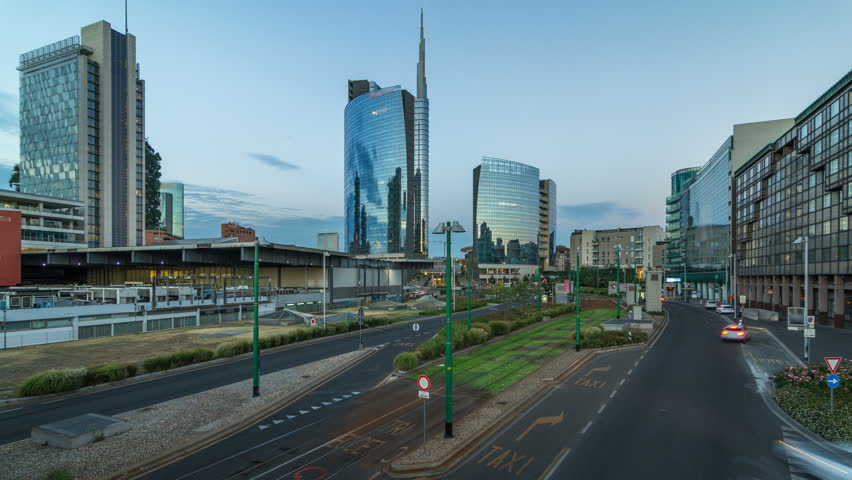 Milan skyline with modern skyscrapers in Porta Nuova business district day to night transition timelapse in Milan, Italy, after sunset. Traffic on the road. Light in windows. Top view from bridge